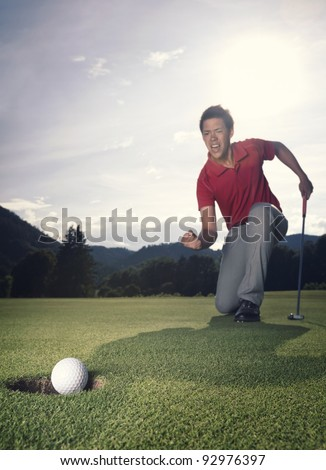 Male golf player in winner pose on green with putter as golf ball drops into hole. - stock photo