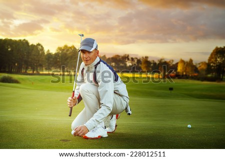 male golf player is putting off a ball from hole - stock photo