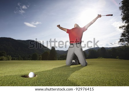 Male golf player on knees and arms raised with putter in hand in winner pose on golf green being overjoyed as golf ball drops into cup. - stock photo