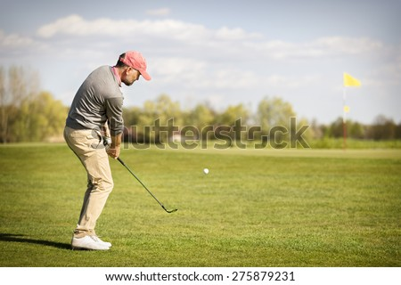 Male golf player pitching ball onto green, with flag in background and copyspace. - stock photo