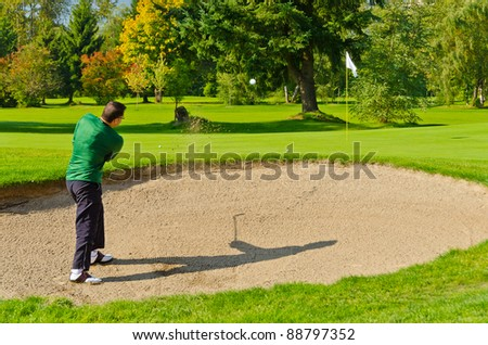 Male golf player pitching off golf ball from the sand bunker, wonderful landscape in background. - stock photo