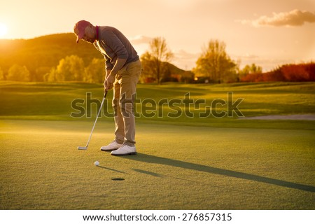 Male golf player putting at green with beautiful fairway at sunset. - stock photo