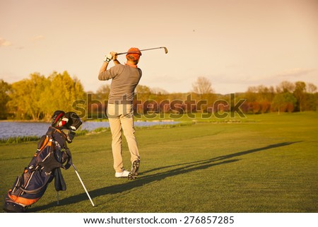 Male golf player shooting ball on fairway at sunset. - stock photo