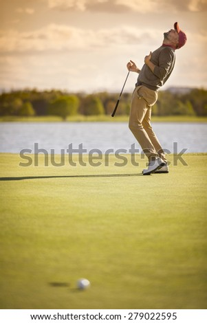 Male golf player showing emotion after ball missing hole at sunset. - stock photo