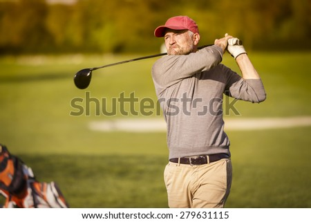 Male golf player swinging driver golf club from tee box at dusk with beautiful atmosphere. - stock photo
