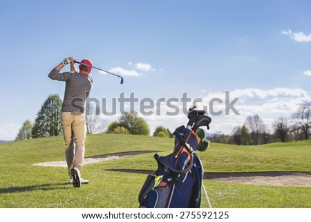 Male golf player swinging golf club, with golf bag and beautiful fairway in background. - stock photo