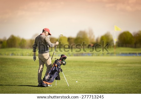 Male golf player taking out golf club from bag, with green and flag in background. - stock photo