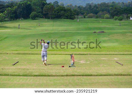 Male golf player teeing off golf balls from tee box, wonderful cloud in background.  - stock photo