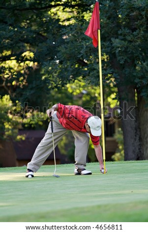 Male golfer bends to retrieve golf ball from hole. - stock photo
