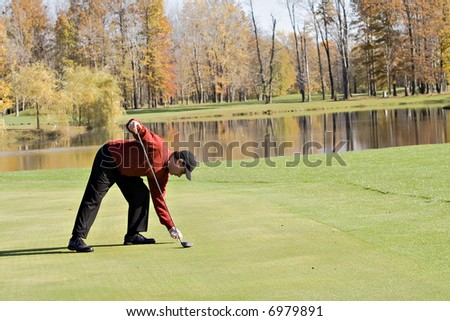 Male Golfer in sweater tees up the ball for a golf shot - Autumn setting - stock photo