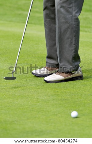 male golfer lining up a putt on the golf green - stock photo