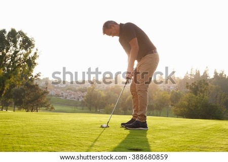 Male Golfer Lining Up Putt On Green - stock photo