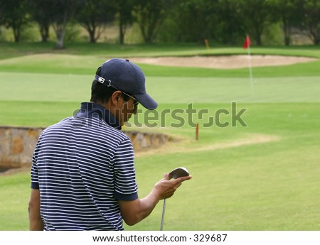 male golfer looking at his club - stock photo