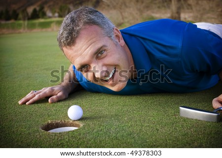 Male Golfer missing the putt - stock photo