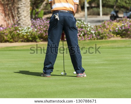 Male golfer on a practice putting green