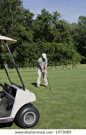 Male golfer on the fairway - golf cart in foreground. - stock photo