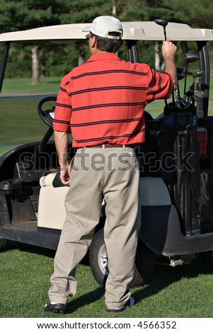 Male golfer picks driver club from golf  bag on back of cart. - stock photo