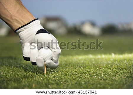 Male golfer places a golf ball and tee in the ground. Horizontal shot. - stock photo