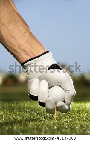 Male golfer places a golf ball and tee in the ground. Vertical shot. - stock photo