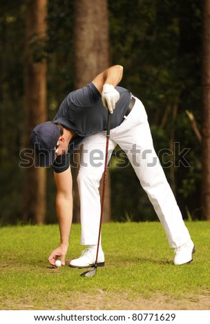 Male golfer places a golf ball on the tee