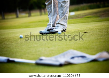 Male golfer putting a golf ball in to hole - stock photo