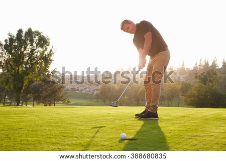Male Golfer Putting Ball Into Hole On Green - stock photo