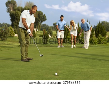 Male golfer putting in golf ball on the green, partners jittering. - stock photo