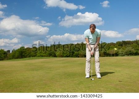male golfer putting on green against blue sky - stock photo