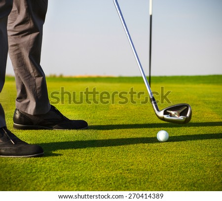 Male golfer putting, selective focus on golf ball - stock photo