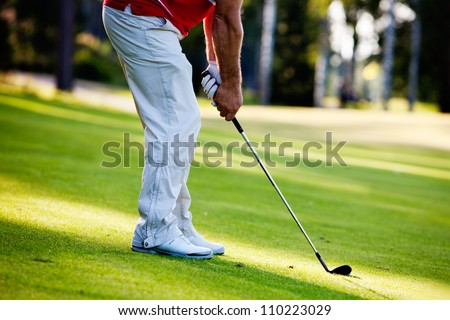 Male golfer shooting a golf ball from green grass - stock photo