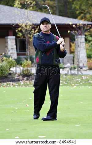 Male golfer tees of  in front of club house on an autumn day. - stock photo