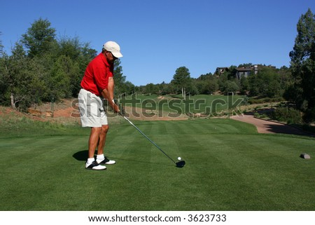 Male golfer with red shirt addressing ball about to tee off - stock photo