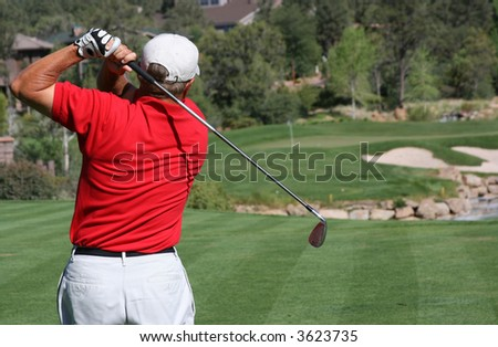 Male golfer with red shirt successfully hitting ball on green with ball and flag visible, focus on golfer - stock photo