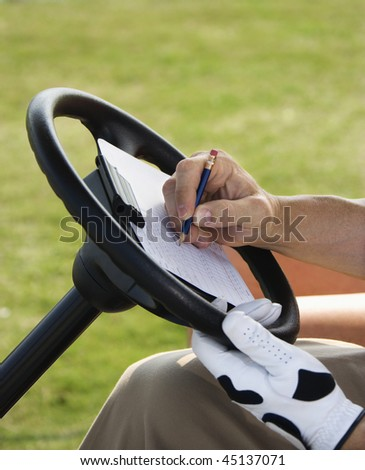 Male golfer writing his golf score while sitting in a golf cart. Vertical shot. - stock photo