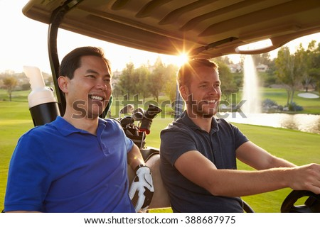 Male Golfers Driving Buggy Along Fairway Of Golf Course - stock photo