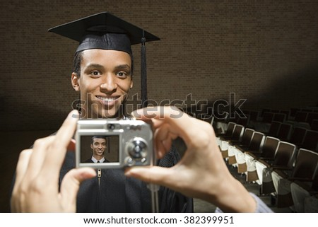 Male graduate being photographed - stock photo