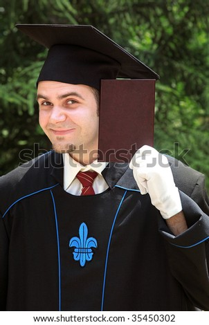 Male graduate holding diploma proudly outdoor - stock photo