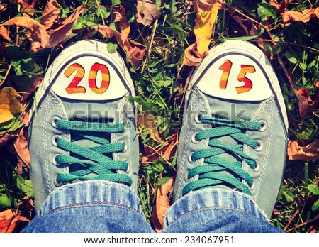 Male green shoes in yellow leafs from above with 2015 sign - stock photo