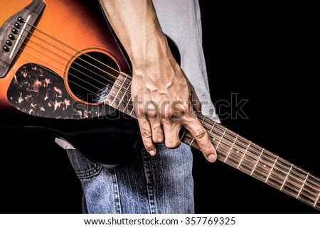 male guitarist holding sunburst acoustic guitar, isolated on black for music background - stock photo