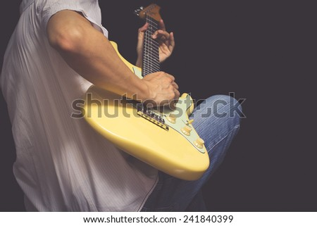 male guitarist / musician plays electric guitar, isolated on black & old color film processed - stock photo