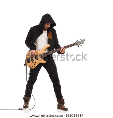 Male guitarist plays the bass giutar. Full length studio shot isolated on white.