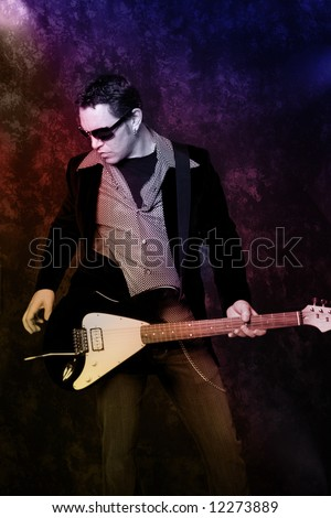 Male guitarist with electric guitar on grunge background