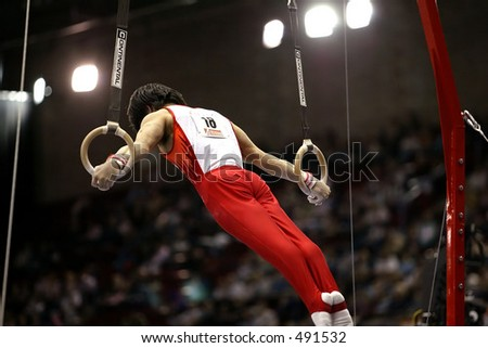 male gymnast on rings with crowd in the background - stock photo