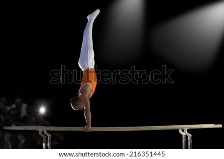 Male gymnast performing handstand on parallel bars, side view - stock photo