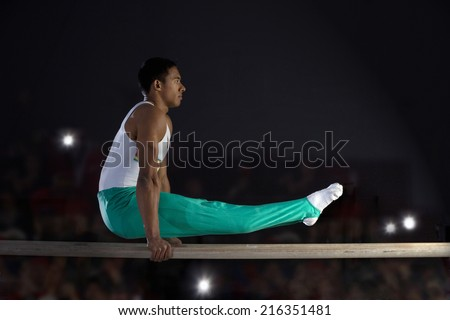 Male gymnast performing on parallel bars, side view - stock photo