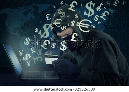 Male hacker wearing mask and using laptop to steal money with credit card and online transaction - stock photo