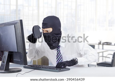 Male hacker wearing mask and using magnifier for finding and steal information on the computer in office - stock photo