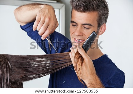 Male hairdresser cutting client's wet hair in salon