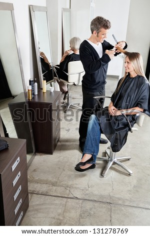 Male hairdresser cutting female client's hair with senior woman in background