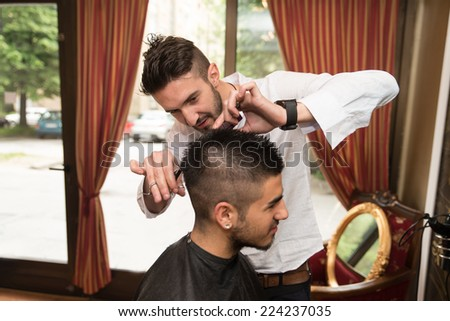 Male Hairdresser Cutting Hair Of Smiling Man Client - Handsome Young Hairdresser Giving A New Haircut To Male Customer At Parlor - stock photo